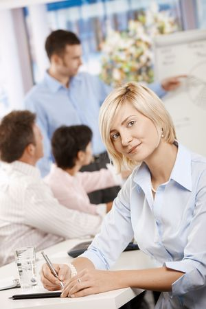 Young businesswoman sitting on business meeting in office making notes, looking at camera smiling. photo