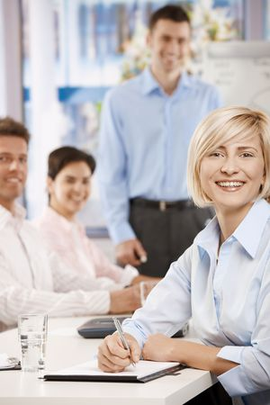 american staff: Happy businesswoman sitting on business meeting in office making notes, looking at camera smiling.