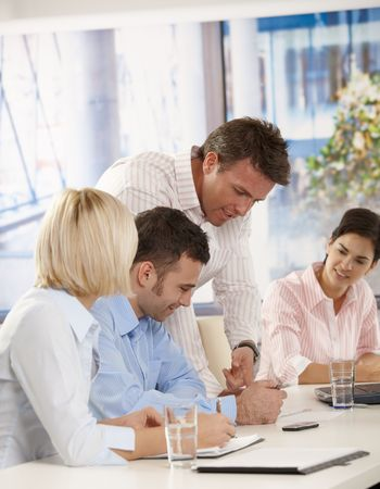 lead: Young businesspeople having business meeting in office boss explaining giving instructions. Stock Photo