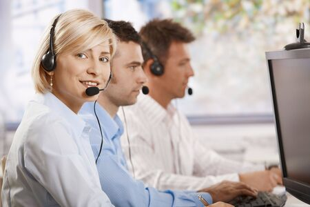 Young female customer service operator talking on headset, looking at camera, smiling. photo