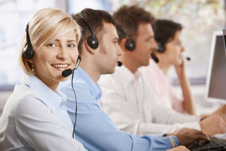 Happy female customer service operator recieving calls on headset, looking at camera, smiling. photo