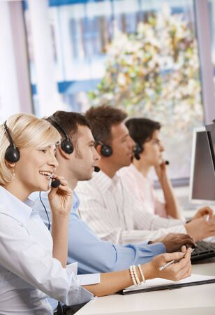Four young customer service operators sitting in a row and talking on headset. photo