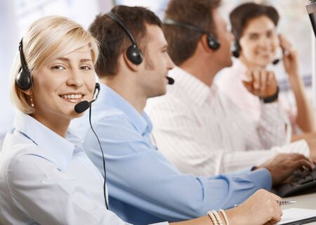Happy young customer service operator talking via headset, smiling people in background. Stock Photo - 6373614