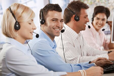 Happy young customer service operator talking via headset, typing on keyboard, looking at camera, smiling. photo