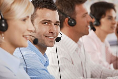 Young customer service operator wearing headset, looking at camera, smiling. photo