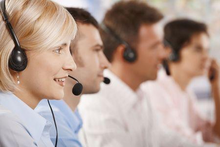servicio al cliente: Cuatro j�venes clientes operadores de servicios sentado en una fila y hablando sobre el kit manos libres port�til.