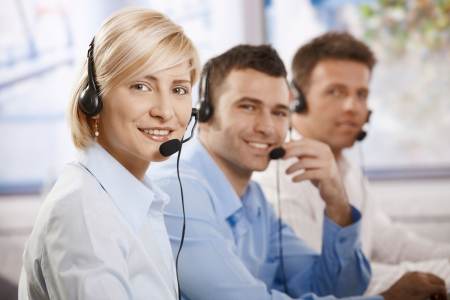 Happy young customer service operators talking on headset, looking at camera, smiling. photo