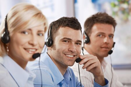 Happy young customer service operators talking on headset, eye contact, smiling. photo