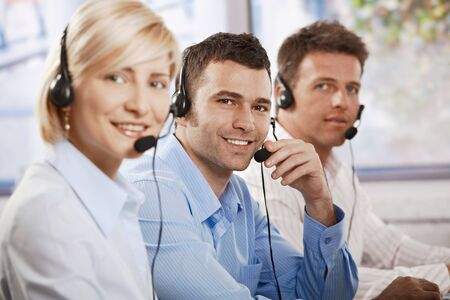 Happy young customer service operators receicving calls on headset, looking at camera, smiling. Stock Photo - 6373759