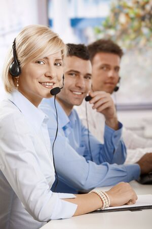 Happy young helpdesk operators receicving calls on headset, looking at camera, smiling. Stock Photo - 6373683