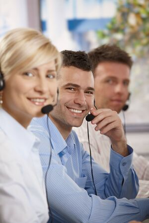 Happy young customer service operators talking on headset, eye contact, smiling. Stock Photo - 6373672