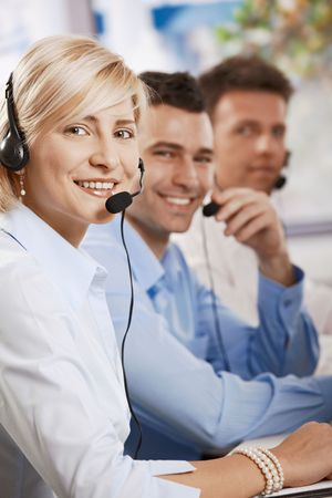 Happy young customer service operators receicving calls on headset, looking at camera, smiling. photo