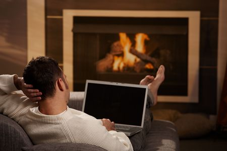 teleworking: Man sitting on sofa at home in front of fireplace and using laptop computer, rear view.