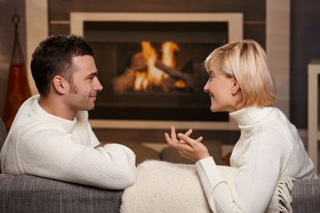 couple talking: Young romantic couple sitting on sofa in front of fireplace at home, looking at each other, talking. Stock Photo
