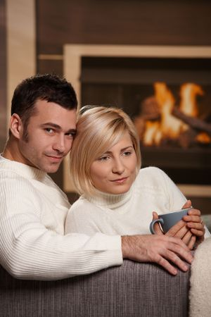 Young couple hugging on sofa in front of fireplace at home, smiling. photo