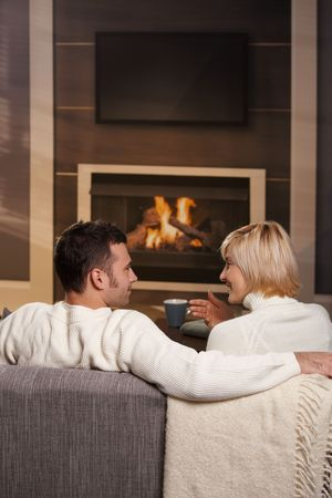 cosy: Young romantic couple sitting on sofa in front of fireplace at home, looking at each other, talking, rear view.