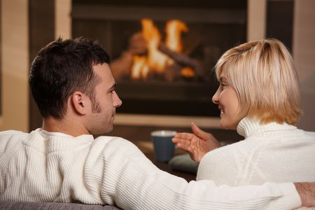 Young romantic couple sitting on sofa in front of fireplace at home, looking at each other, talking, rear view. photo