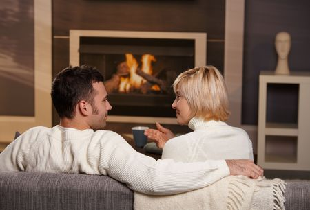 warm cloth: Young romantic couple sitting on sofa in front of fireplace at home, looking at each other, talking, rear view.