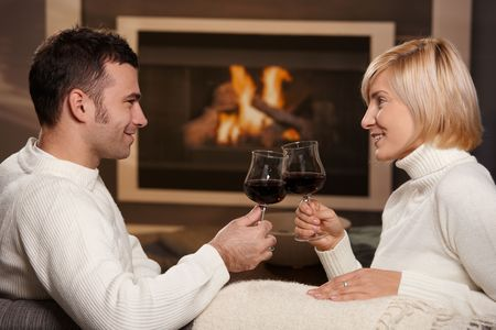Young romantic couple sitting on sofa in front of fireplace at home, drinking red wine. Stock Photo - 6373820