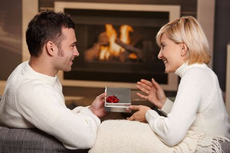 fireside: Young romantic couple sitting on couch in front of fireplace at home, man giving gift, side view.