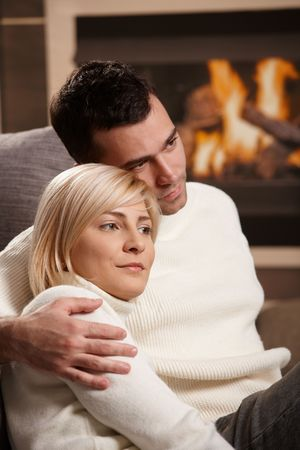 Young couple hugging on sofa in front of fireplace at home, looking away, smiling. photo