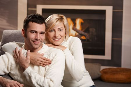 warm cloth: Young couple hugging on sofa in front of fireplace at home, looking at camera, smiling.
