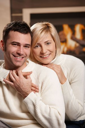Young couple hugging on sofa in front of fireplace at home, looking at camera, smiling. Stock Photo - 6373661