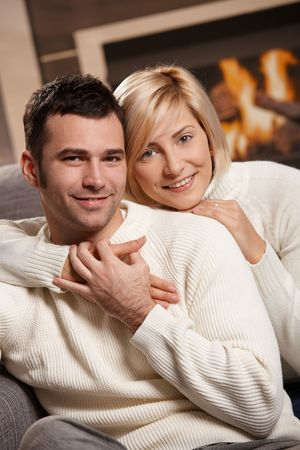 Young couple hugging on sofa in front of fireplace at home, looking at camera, smiling. photo