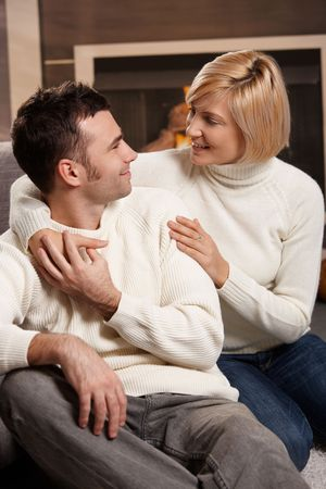 Young couple hugging on sofa in front of fireplace at home, looking at each other, smiling. Stock Photo - 6373812