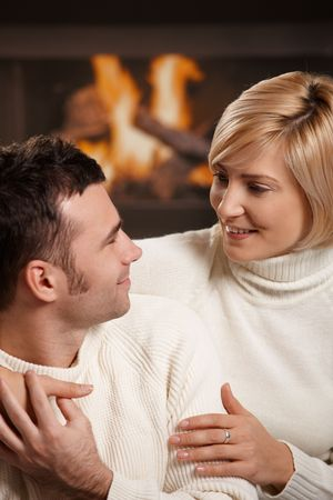 Young couple hugging on sofa in front of fireplace at home, looking at each other, smiling. photo