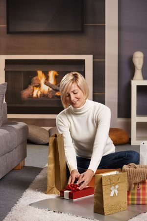 Woman siiting on floor at home in front of fireplace wrapping presents for Chrismas. Stock Photo - 6373802
