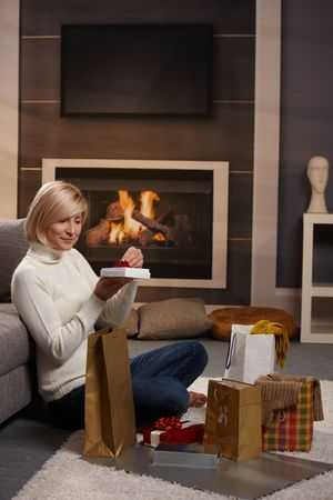Woman siiting on floor at home in front of fireplace wrapping presents for Chrismas. photo