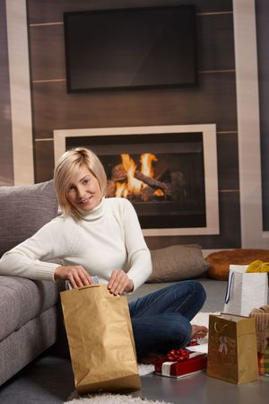 Woman siiting on floor at home in front of fireplace wrapping presents for Chrismas. Stock Photo - 6373788