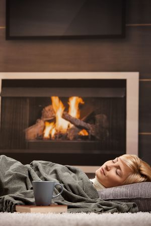 Woman sleeping at home lying on floor in front of a fire place, photo