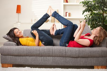 red jeans: Smiling teens lying on couch with feet put together playing with mobile phone listening to music.