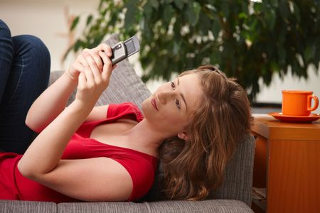 Happy teen girl looking at phone lying on couch at home. photo