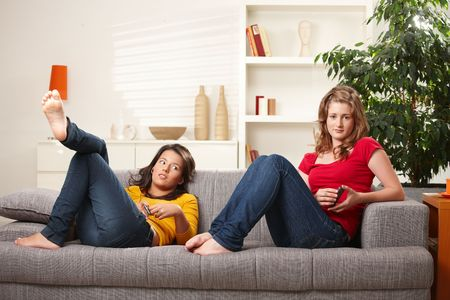 Teen girls relaxing on sofa at home listening to music. Stock Photo - 6373954