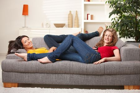 lay down: Happy teen girls lying on sofa together smiling at camera having rest at home.