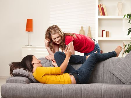 women in jeans: Smiling teen girls listening music together on earphones at home. Stock Photo