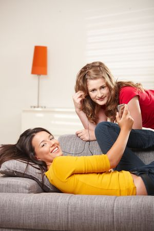 Teen girls listening music together on earphones at home, looking at camera smiling. photo