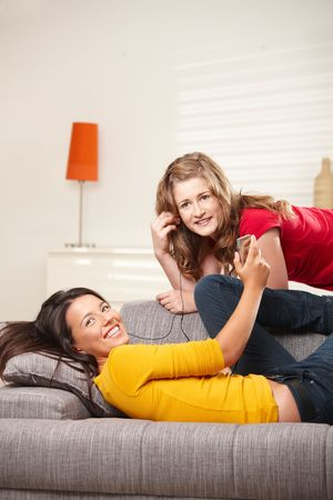 Happy teen girls listening music together at home, looking at camera smiling. photo