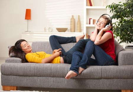 teens playing: Teen girls listening music on earphones and headphones sitting together on couch  at home with closed eyes smiling. Stock Photo