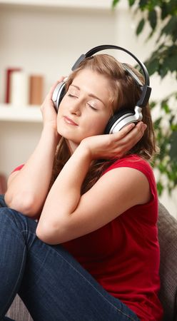 Teen girl listening to music on headphones with eyes closed smiling. photo
