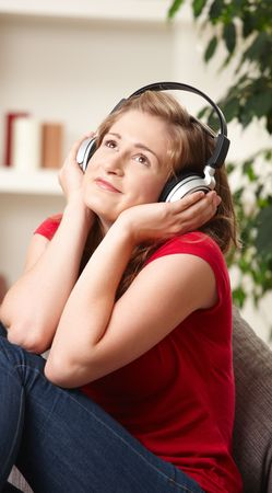 Happy teen girl listening to music on headphones sitting on couch at home smiling. photo