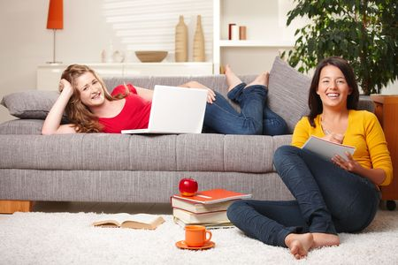 Happy schoolgirls studying together in living room with books and computer, laughing. Stock Photo - 6374063