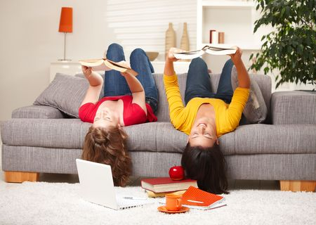 Teenage girls sitting upside down on sofa reading books. photo