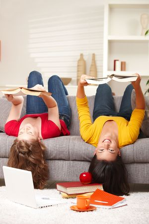Teenage girls sitting upside down on sofa smiling holding books. photo