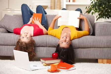 Happy teen girls sitting upside down on sofa smiling looking at camera holding books. photo