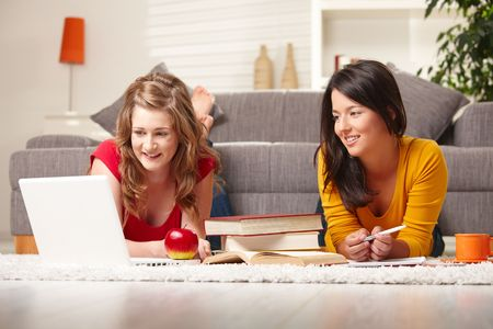 Smiling teen girls sitting on floor of living room smiling looking at laptop. photo