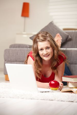 Happy teen girl lying on floor with laptop smiling at camera. photo